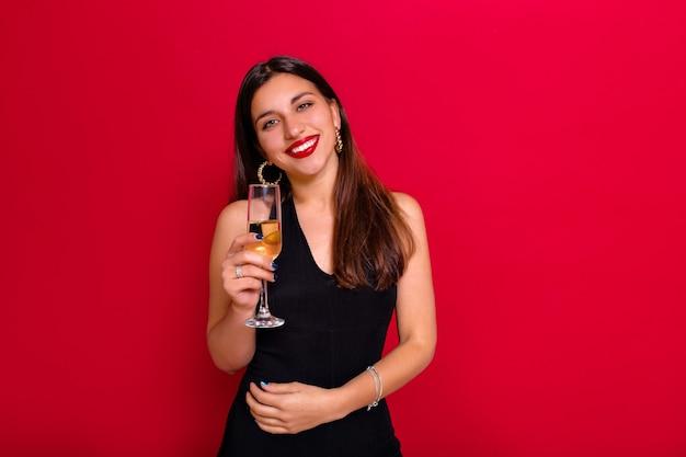 Studioporträt der anmutigen frau in der trendigen kleidung, die auf einer party kühlt.