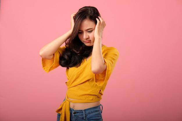 Studioporträt der asiatischen frau in der freizeitbekleidung, die betontem unglücklichem niedergedrücktem glaubt