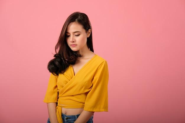 Studioporträt der asiatischen frau in der freizeitbekleidung, die traurigem unglücklichem niedergedrücktem glaubt