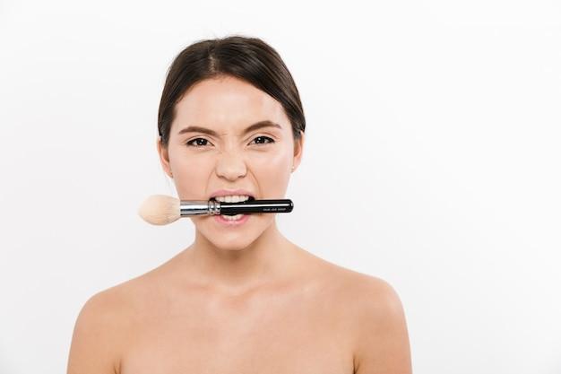 Studioporträt der fröhlichen asiatischen frau, die halbnackt ist und make-up-pinsel, in ihrem mund, lokalisiert über weiß