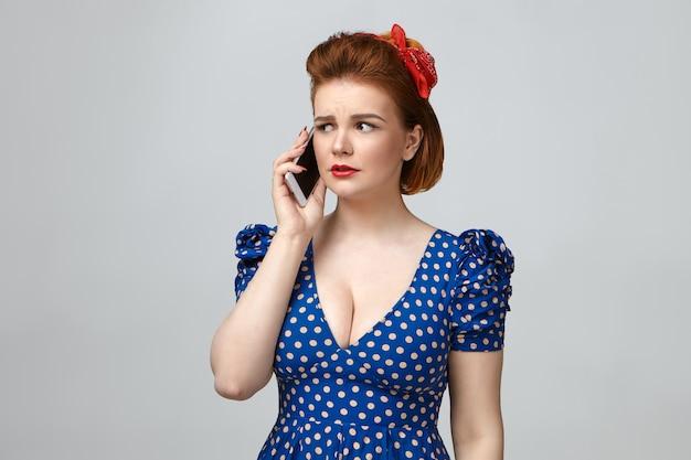Studioporträt der frustrierten schönen jungen hausfrau, die helles make-up und retro gepunktetes kleid mit niedrigem schnitt trägt, das besorgten gesichtsausdruck hat