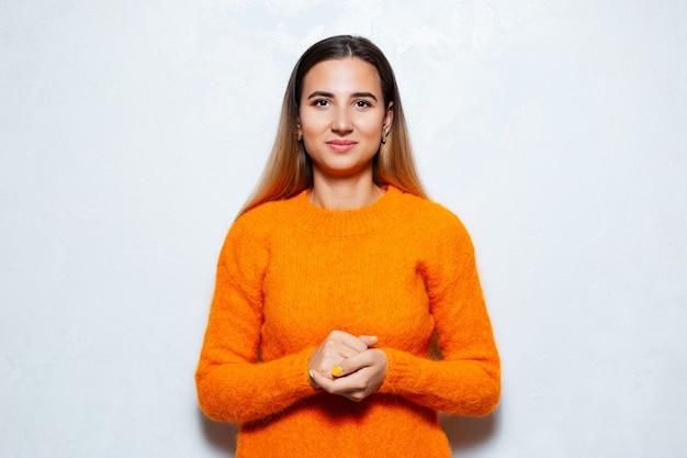 Studioporträt der geschäftsfrau im orangefarbenen pullover auf weißer oberfläche