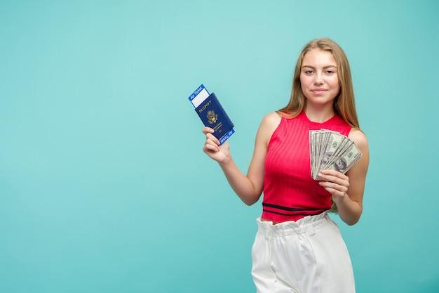 Studioporträt der hübschen jungen studentin, die pass mit tickets und geld hält, lokalisiert auf hellblauem hintergrund