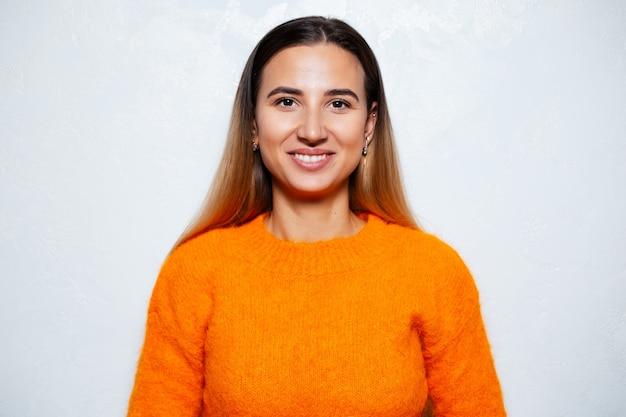 Studioporträt der jungen brünetten lächelnden frau, die orange pullover trägt