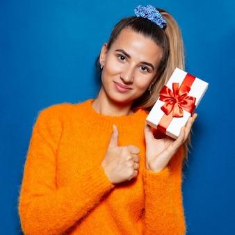 Studioporträt der jungen frau, die weiße geschenkbox mit roter schleife hält, zeigt daumen oben