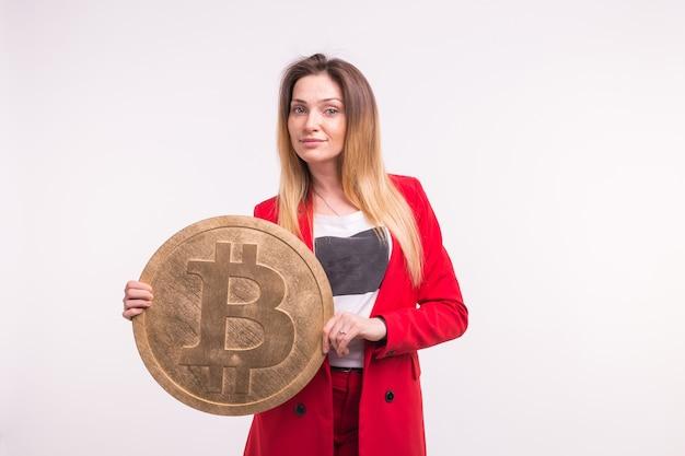 Studioporträt der jungen geschäftsfrau mit bitcoin.