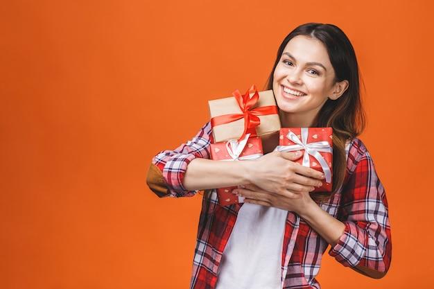 Studioporträt der lächelnden jungen schönen frau hält rote geschenkboxen. isoliert gegen orange hintergrund.