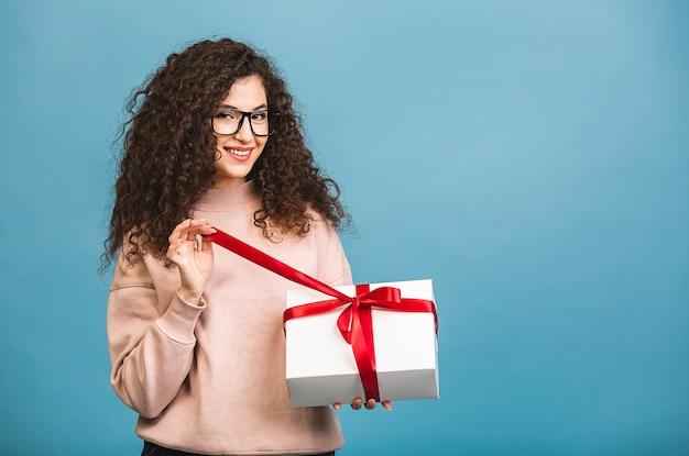 Studioporträt der lächelnden lockigen jungen schönen frau hält geschenkbox. isoliert über blauem hintergrund.