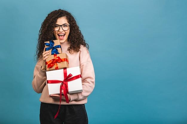 Studioporträt der lächelnden lockigen jungen schönen frau hält geschenkboxen. isoliert über blauem hintergrund.