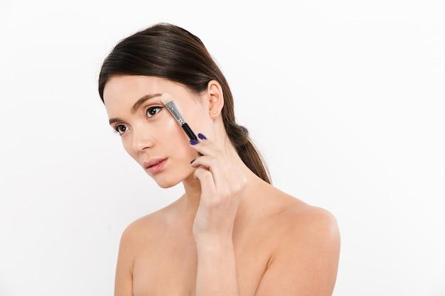 Studioporträt der schönen asiatischen frau mit weicher haut, die lidschatten mit make-up-pinsel anwendet, lokalisiert über weiß