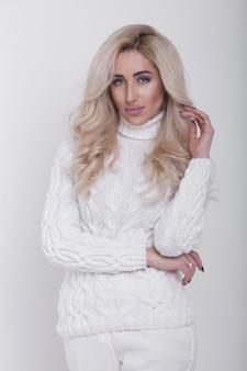 Studioporträt der schönen langhaarigen blonden frau im heißen pullover auf weißem hintergrund