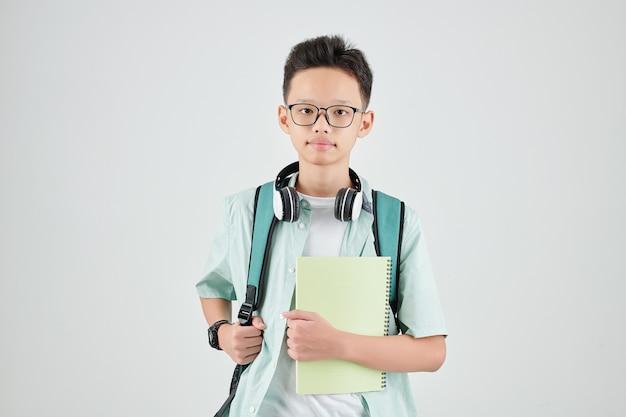 Studioporträt des ernsten asiatischen schuljungen mit dem rucksack, der das lehrbuch hält und schaut