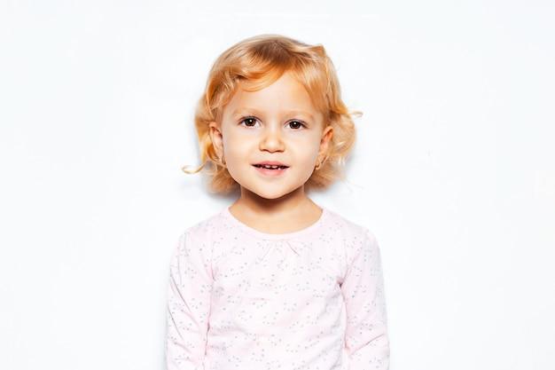 Studioporträt des fröhlichen kindermädchens mit den lockigen blonden haaren