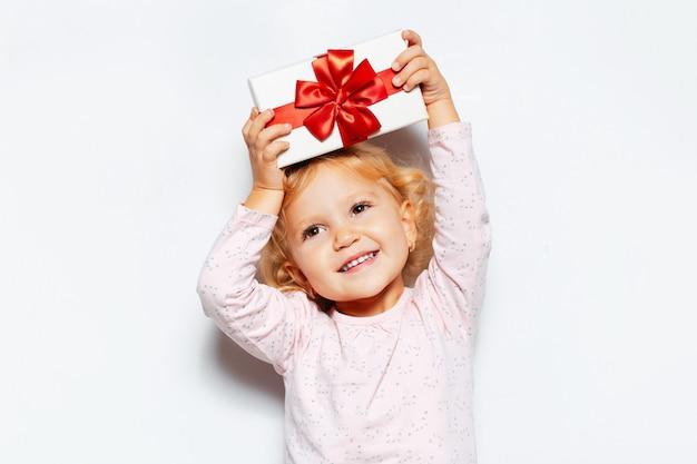 Studioporträt des glücklichen kindermädchens, das geschenkbox mit roter schleife über dem kopf hält