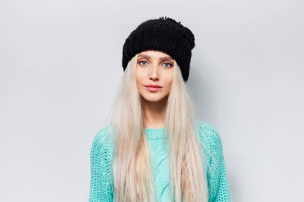 Studioporträt des hübschen blonden mädchens, das blauen pullover und schwarzen hut auf weißem hintergrund trägt.
