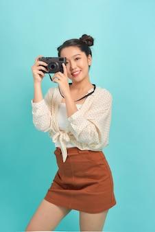Studioporträt des hübschen jungen mädchens, das fotokamera hält