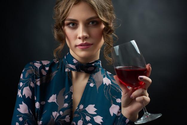 Studioporträt des hübschen mädchens blaues kleid mit stilvollem blumendruck hioding rotweinglas tragend