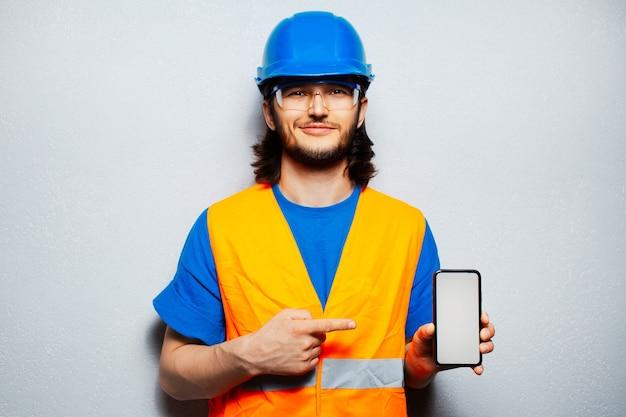 Studioporträt des jungen bauarbeiteringenieurs, der sicherheitsausrüstung trägt und finger auf smartphone zeigt