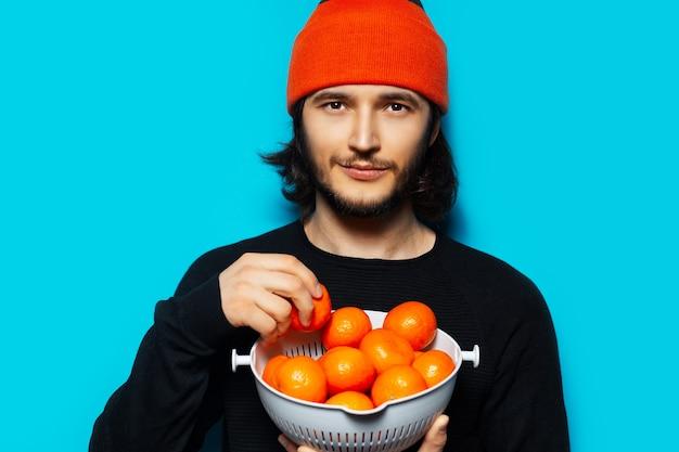 Studioporträt des jungen mannes, der den orangefarbenen mützenhut trägt und eine schüssel mandarinen hält. auf dem hintergrund der blauen wand.