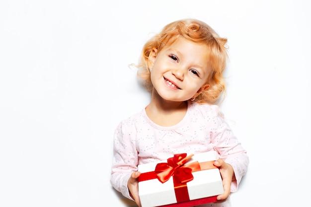 Studioporträt des kindermädchens, das geschenkbox auf weißer wand hält