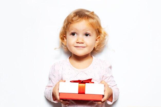 Studioporträt des kindermädchens, das geschenkbox mit roter schleife hält