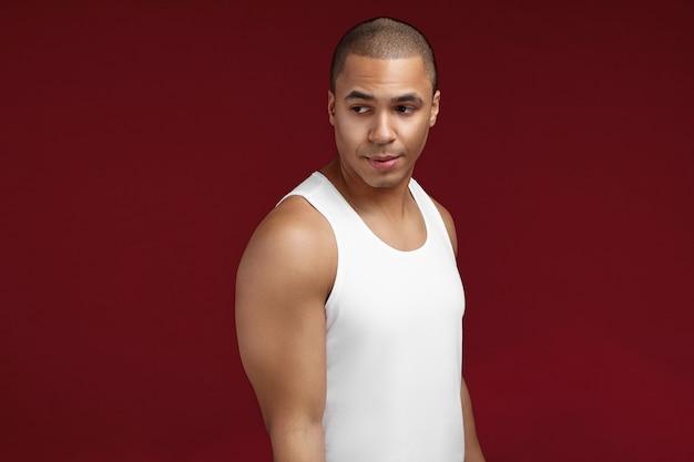 Studioporträt des kühlen selbstbewussten jungen afroamerikanischen 20-jährigen mannes, der weißes ärmelloses t-shirt trägt, das lokal aufwirft. hübscher ernsthafter dunkelhäutiger kerl mit muskulösen schultern, die drinnen ruhen