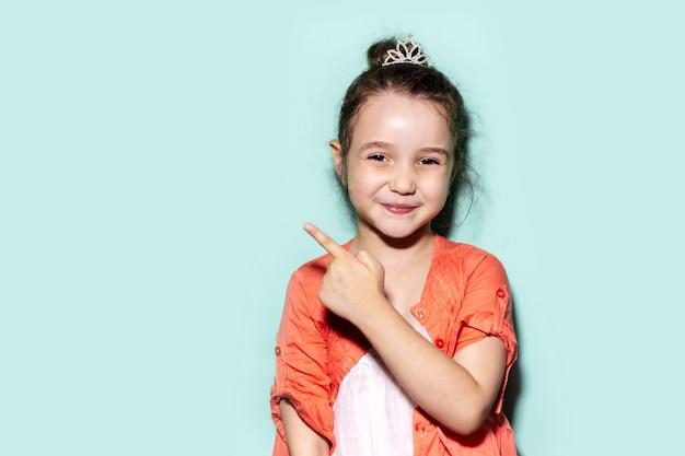 Studioporträt des lächelnden kleinen kindermädchens, das mit dem finger auf den leeren hintergrund der farbe aqua menthe mit kopienraum zeigt