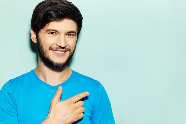 Studioporträt des lächelnden mannes, der mit dem finger auf dem leeren raum des blauen hintergrunds zeigt.
