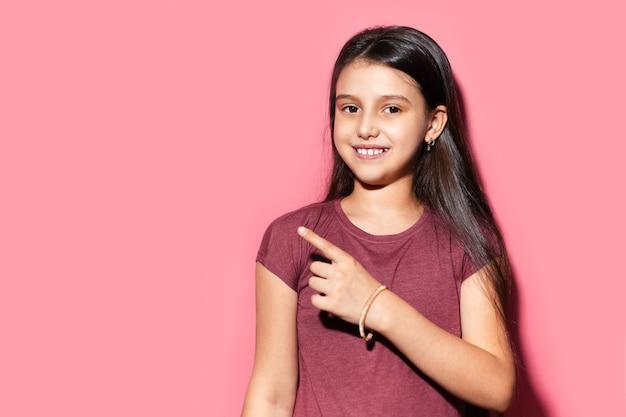 Studioporträt des lächelnden teenager-mädchens, das mit dem finger auf leeren hintergrund der pastellrosa-farbe mit kopienraum zeigt.