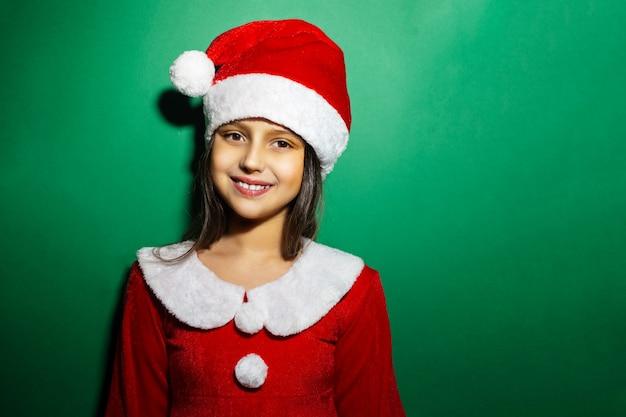 Studioporträt des lächelnkinderkindes, das rotes kostüm des weihnachtsmanns auf grüner oberfläche trägt