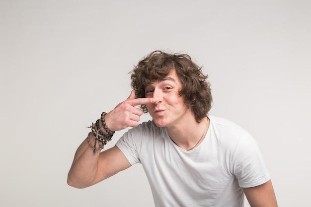Studioporträt des lustigen jungen mannes, der auf seine nase im weißen t-shirt zeigt.