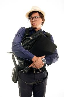 Studioporträt des mannes in den gläsern auf einem weißen raum, ein verlorener tourist, der taschen umarmt und wegschaut