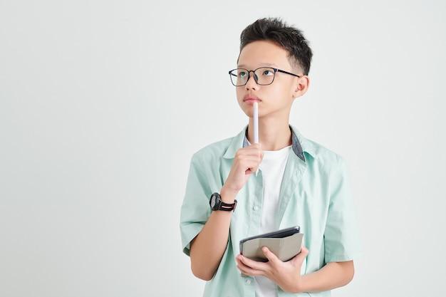 Studioporträt des nachdenklichen vietnamesischen schülers mit tablet-computer und stift, die nach oben schauen