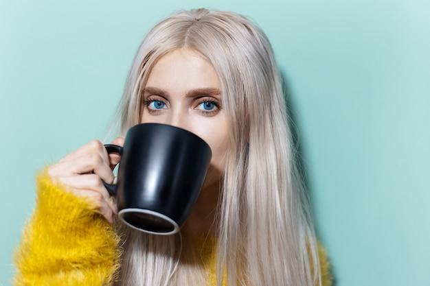 Studioporträt des schönen blonden mädchens mit den blauen augen, die tee von der schwarzen tasse trinken, gelben pullover auf cyan, aqua menthe farbe tragend.
