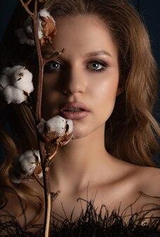 Studioporträt des schönen blonden modells mit perfekter haut und make-up, das im schatten posiert
