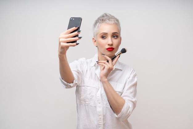 Studioporträt des schönen trendigen mädchens mit kurzen haaren und make-up