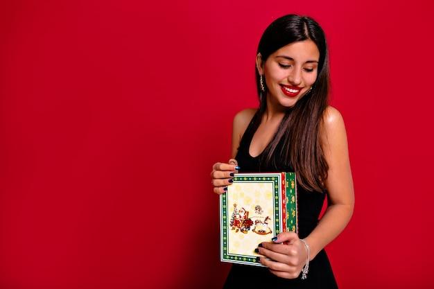 Studioporträt einer bezaubernden hübschen brünetten dame mit langen haaren, die schwarzes kleid tragen und weihnachtsgeschenk auf lokalisiertem rotem hintergrund halten