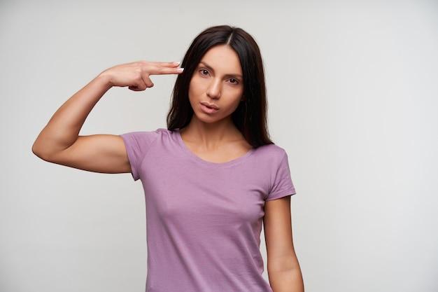 Studioporträt einer jungen braunäugigen hübschen brünetten frau, die hand mit pistolengeste zu ihrem kopf hebt und ernst schaut, gegen weiß stehend