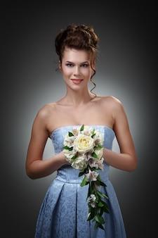 Studioporträt einer schönen braut in einem blauen kleid mit einem strauß von rosen und orchideen.