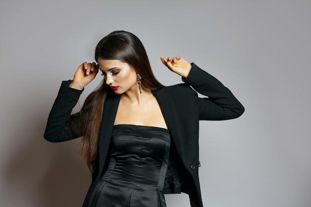 Studioporträt einer schönen frau mit langen haaren trägt seidenkleid und jacke. freiraum
