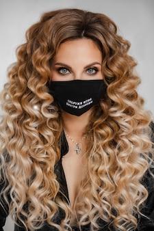 Studioporträt einer stilvollen, schönen kaukasischen frau mit langen lockigen haaren, die eine schwarze schutzmaske mit einem darauf gedruckten text trägt. mode ist draußen, depression ist drinnen.