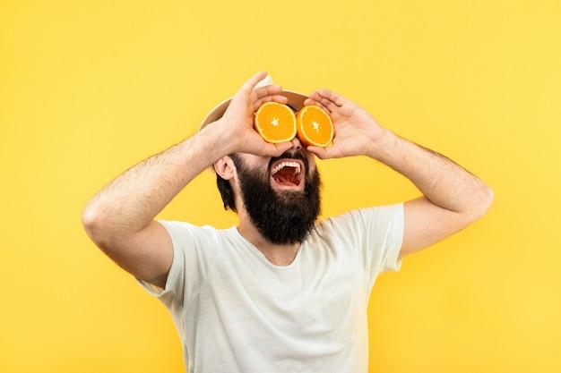Studioporträt eines bärtigen mannes in panama, brille mit orangenscheiben darstellend