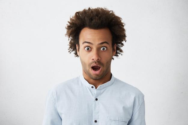 Studioporträt eines dunkelhäutigen mannes mit bug-eyed mit buschigem dunklem haar und borsten, die mit überraschung schauen