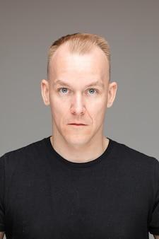 Studioporträt eines erwachsenen blonden kaukasischen mannes mit kurzem haarschnitt im schwarzen t-shirt mit blauen augen, die auf grauem hintergrund in die kamera starren.