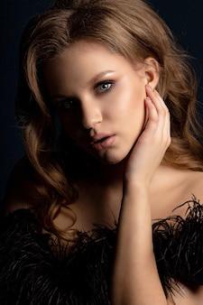 Studioporträt eines glamourösen blonden models mit perfekter haut und make-up, das im schatten posiert