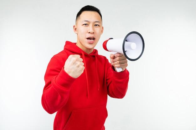 Studioporträt eines jungen asiatischen mannes in einem roten kapuzenpulli mit einem lautsprecher in seinen händen auf einem weißen hintergrundstudio.