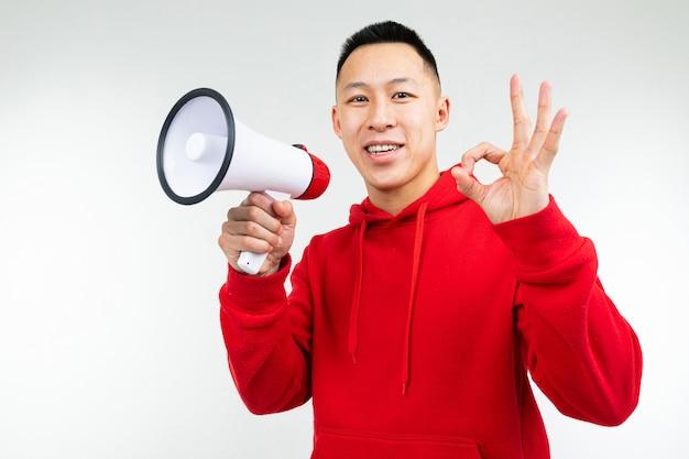 Studioporträt eines jungen asiatischen mannes in einem roten kapuzenpulli mit einem lautsprecher in seinen händen auf einem weißen studio