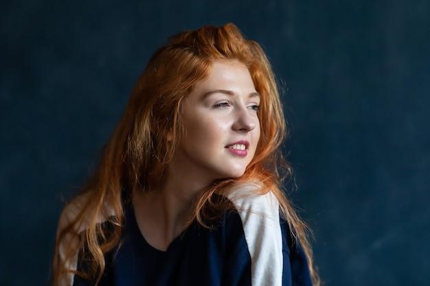 Studioporträt eines jungen rothaarigen schönen mädchens. emotionen einer frau auf blauem hintergrund. karte der emotionen.