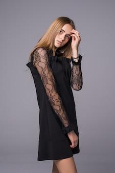Studioporträt eines schönen jungen mädchens, das ein schwarzes kleid trägt