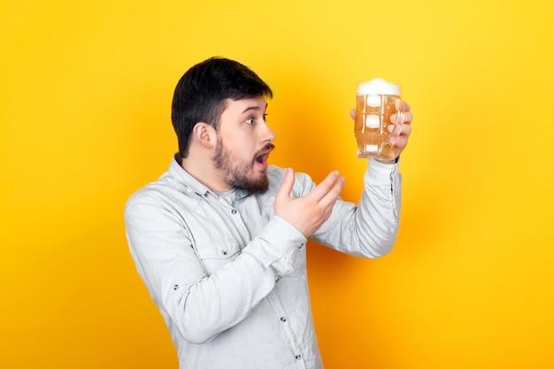 Studioporträt eines überraschten mannes, der über die qualität des bieres empört ist, über gelber wand